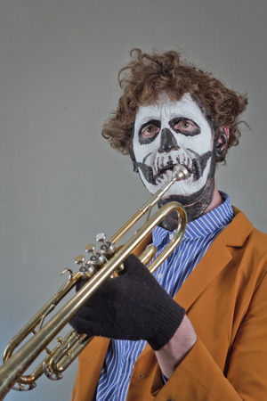Crying trumpet player with face painted as human skull Stock Photo