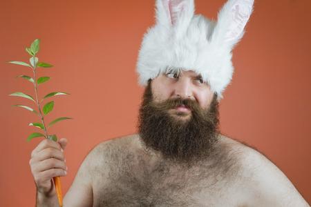 disapproving: Uomo disapprovazione indossa coniglio orecchie e detiene la carota Archivio Fotografico