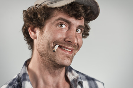 Creepy redneck grinning an evil grin while smoking a cigarette
