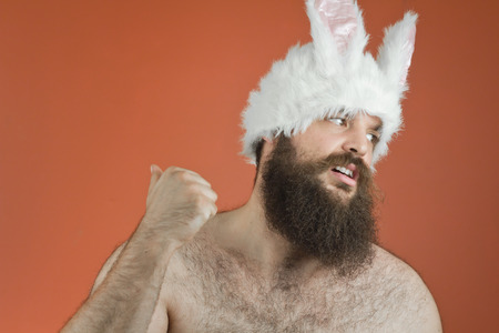 silly: Blaming bearded fat man wears silly bunny ears Stock Photo
