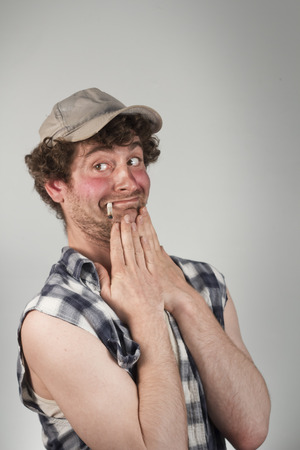 mouthing: Embarrassed smoking redneck blushes as his crush passes Stock Photo