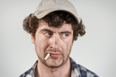 disapproving: Disapproving redneck glances over his shoulder while smoking his cigarette Stock Photo