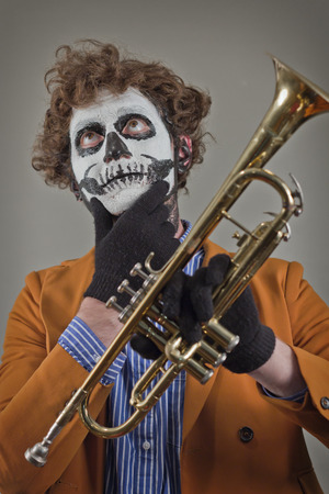 trumpet player: Thinking trumpet player with face painted as human skull