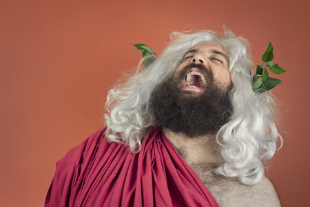 Laughing zeus god or jupiter against orange background Stock Photo