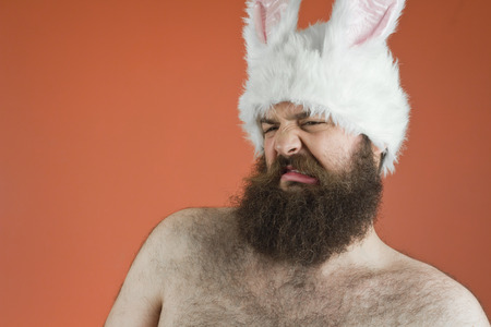 disgusted: Disgusted bearded fat man wears silly bunny ears