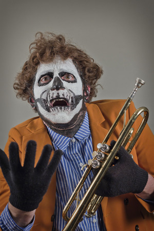 Pleading trumpet player with face painted as human skull