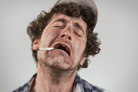 mouthing: Crying redneck sobs and wails while smoking a cigarette Stock Photo