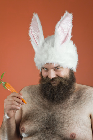 mouthing: Sarcastic bearded fat man wears silly bunny ears