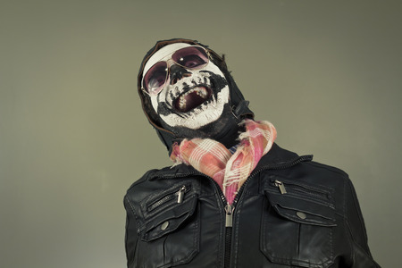 obnoxious: Laughing aviator with face painted as human skull