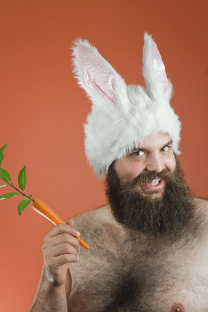 Grinning bearded fat man wears silly bunny ears Imagens