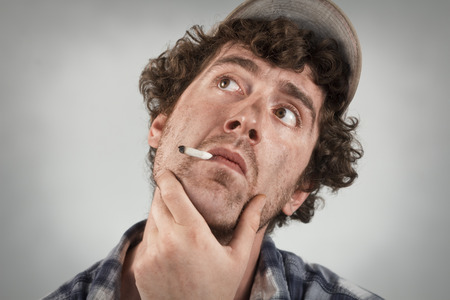 redneck: Thinking redneck dwells on many thoughts as he smokes a cigarette Stock Photo