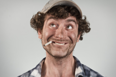redneck: Silly redneck smokes cigarette and bites lip thinking of good fortune