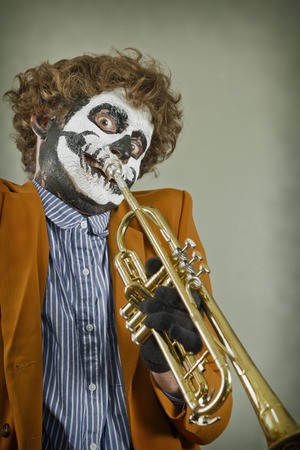 Professional trumpet player with face painted as human skull Stock fotó