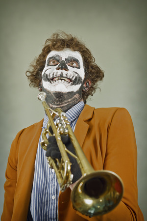 trumpet player: Professional trumpet player with face painted as human skull Stock Photo