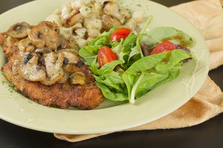 Wiener Schnitzel con champiñones salteados patatas fritas y ensalada fresca Foto de archivo - 41546495