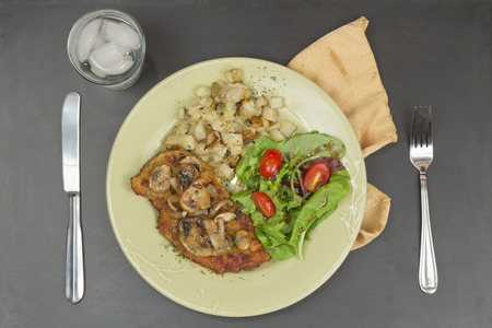 wiener: Wiener schnitzel with sauteed mushrooms home fries and fresh salad Stock Photo