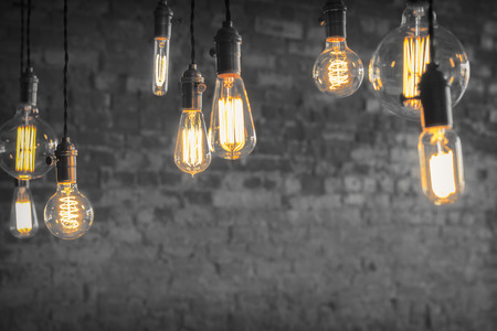 Decorative antique edison style filament light bulbs against brick wall
