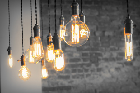 light bulb idea: Decorative antique edison style filament light bulbs against brick wall