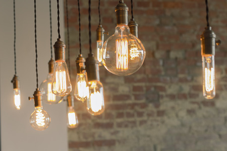 Decorative antique edison style filament light bulbs against brick wall Imagens - 42134201