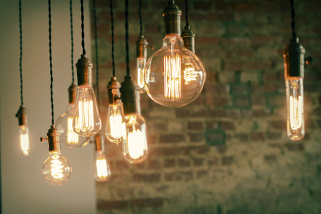 golden light: Decorative antique edison style filament light bulbs against brick wall