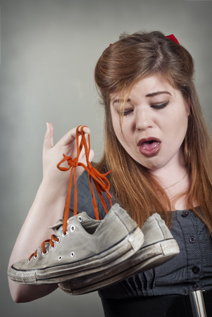 Cute girl holds up two smelly stinky sneaker shoes