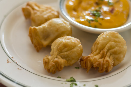 jewish cuisine: Fancy potato knish arranged on plate with cheese sauce Stock Photo