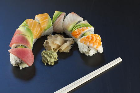 Rainbow sushi roll sliced with wasabi and fresh ginger