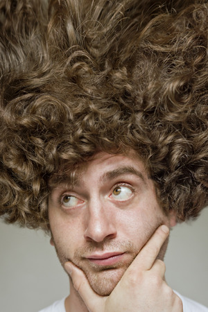 brunette hair: Scruffy faced man with messy curly hair afro Stock Photo