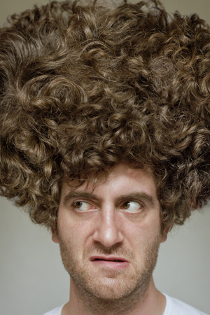 haircut: Scruffy faced man with messy curly hair afro Stock Photo