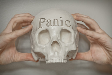 death head holding: Engraved word panic on skull forehead with hands clasping to emphasize this feeling