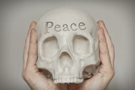 death head holding: Hands hold skull with word peace engraved on forehead