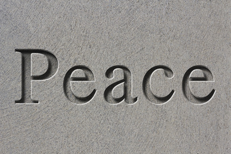 chiseled: Engraving spelling the word Peace on textured old surface