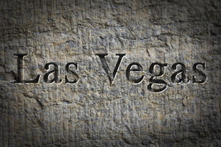 chiseled: Engraving spelling the city Las Vegas on textured old surface