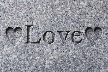 Engraving spelling the word Love on textured old surface Reklamní fotografie