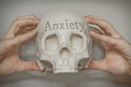 death head holding: Engraved word anxiety on skull for conceptual imagery Stock Photo