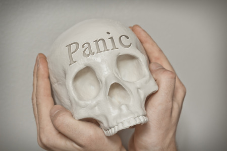 emphasize: Engraved word panic on skull forehead with hands clasping to emphasize this feeling