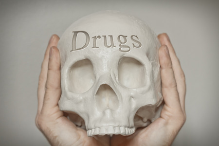 death head holding: Engraved word drugs on skull spell out cause of death