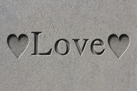 etch: Engraving spelling the word Love on textured old surface Stock Photo