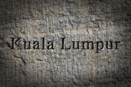 etch: Engraving spelling the city Kuala Lumpur on textured old surface