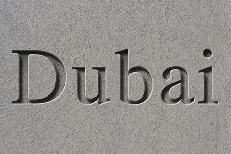 Engraving spelling the city Dubai on textured old surface 版權商用圖片