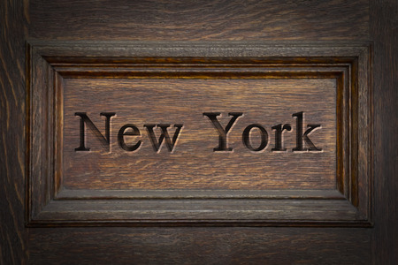 etch: Engraving spelling the city New York on textured old surface