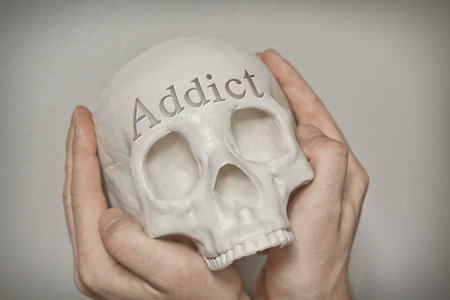 cause: Engraved word Addict on skull spell out cause of death