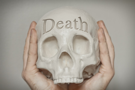 death head holding: Engraved word Death on skull emphasizing this concept