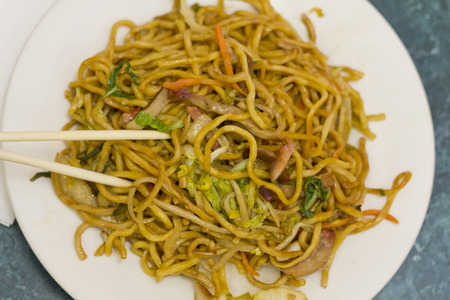 lo mein: Eating Chinese pork lo mein noodles with chopsticks