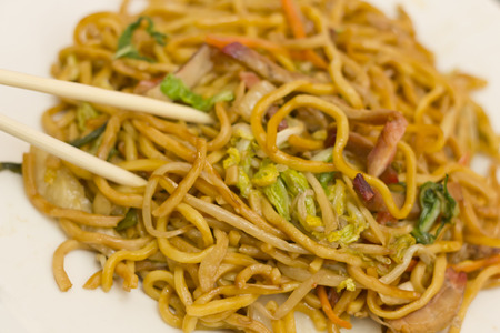 mian: Eating Chinese pork lo mein noodles with chopsticks