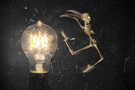 horrifying: Horrifying vintage Halloween themed skeleton jumping past lightbulb Stock Photo