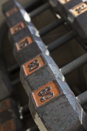 dumb bells: Various sizes and weights of used textured and old dumbbells at gym