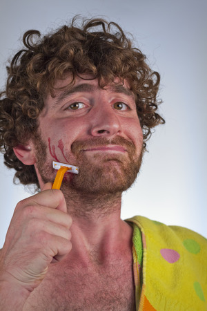 coward: Silly bearded man cuts his face while shaving off his beard Stock Photo