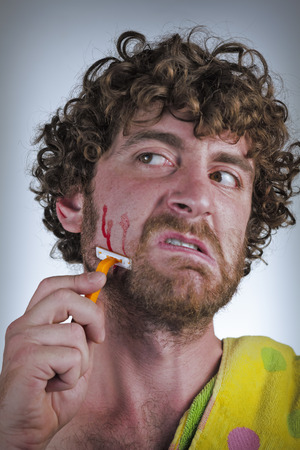 off cuts: Silly bearded man cuts his face while shaving off his beard Stock Photo