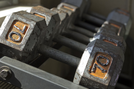 Various sizes and weights of used textured and old dumbbells at gym